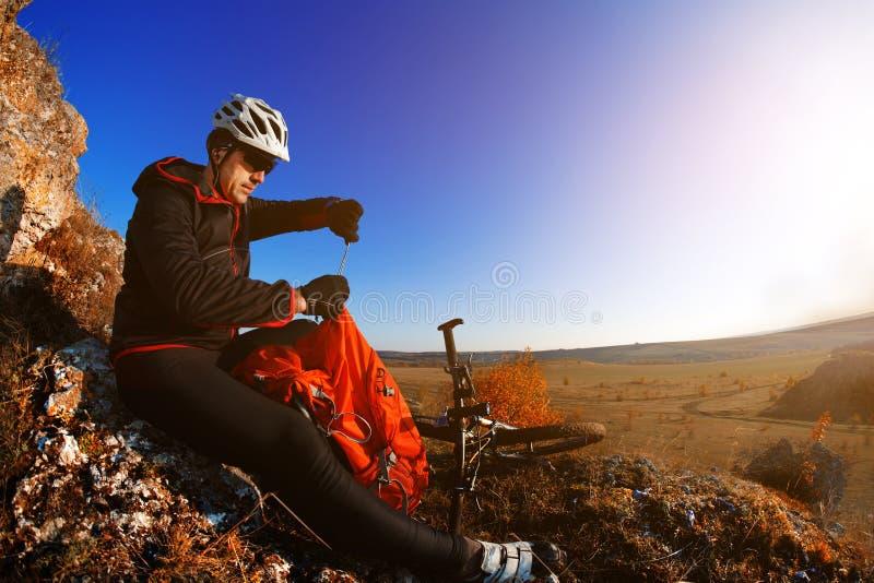 Bergcyklist som ser sikt på cykelslinga i vårlandskap Manlig ryttare som vilar på att cykla tur i natur arkivbild