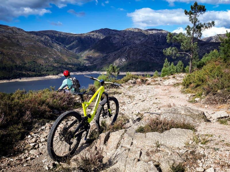 Bergcyklisten beskådar sjön arkivfoto