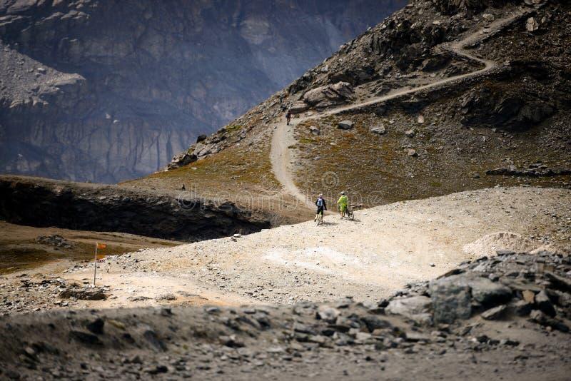 Bergcyklister som ser sikt på cykelslinga i sommar Switzerl arkivfoto