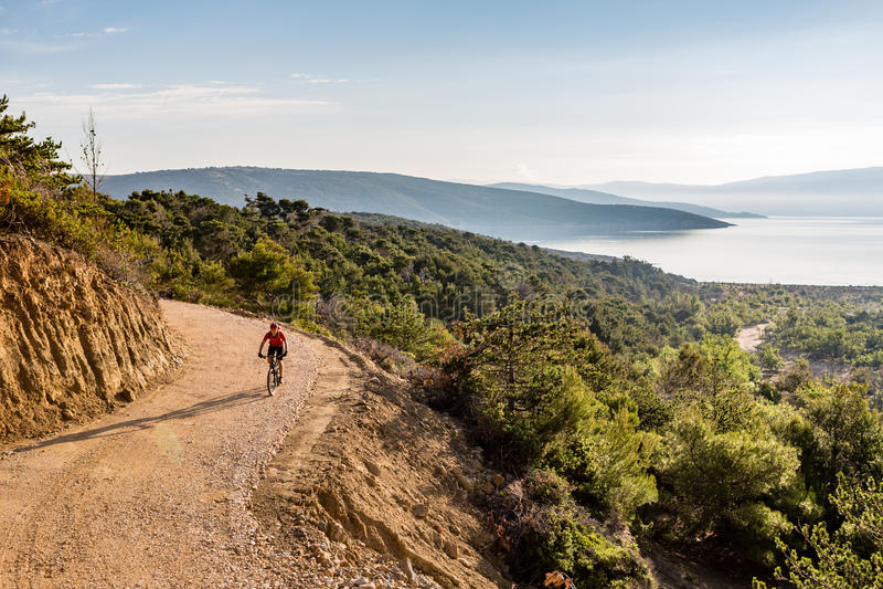 Bergcyklistridning på cykeln i sommarsolnedgångträn arkivfoto