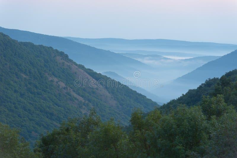 Bergdal i dimman som är horisontal. fotografering för bildbyråer