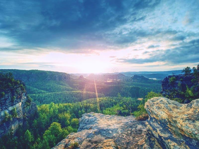 Bergdal under guld- soluppgång Moln över skogen royaltyfri fotografi