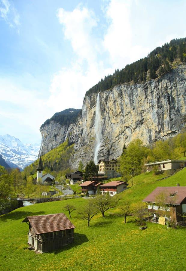 Bergdorf mit Kirche und Wasserfall, Alpen, die Schweiz. stockfotos