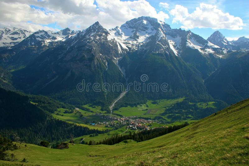 Bergdorf mit schneebedeckten Spitzen stockbilder