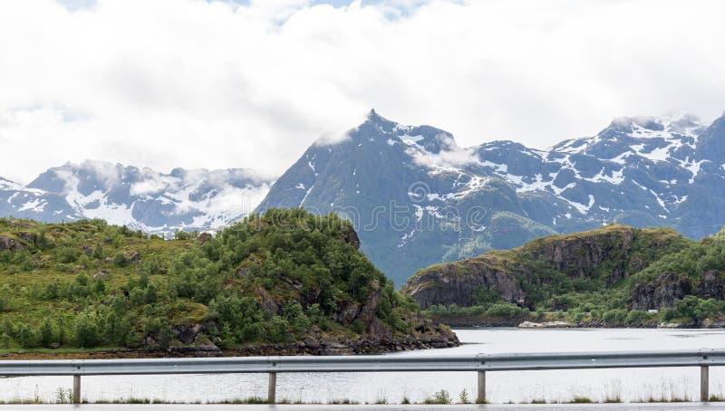 Berge bedeckt durch Schnee im mittleren des Sommers in Fjorden Norwegens Lofoten lizenzfreie stockfotos