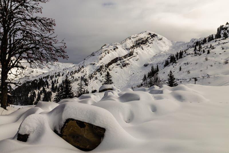 Berge bedeckt mit Schnee und durch Wolken umgeben stockbilder