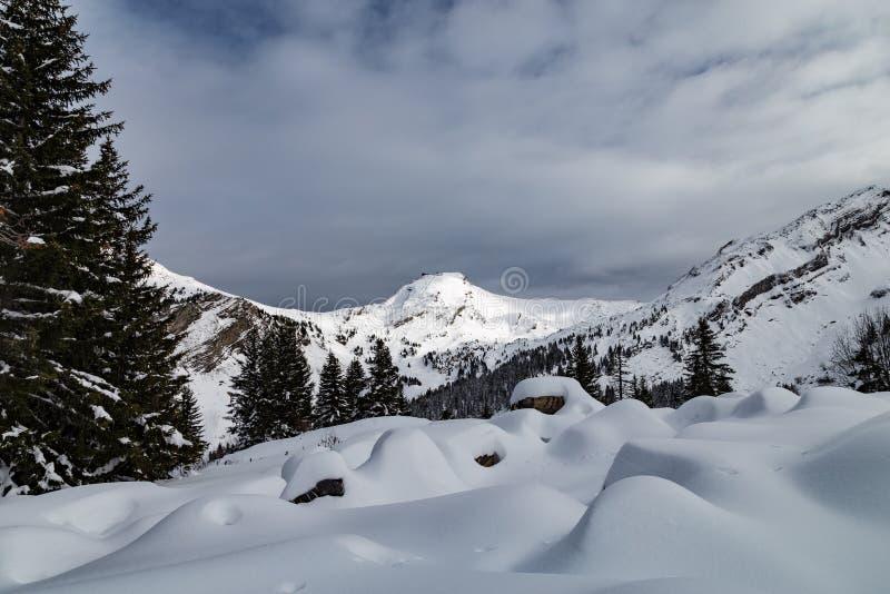 Berge bedeckt mit Schnee und durch Wolken umgeben lizenzfreies stockbild