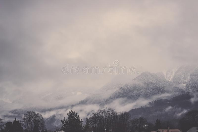 Berge der Bernen Alpen bedeckt im Nebel unter grauem Himmel stockbilder