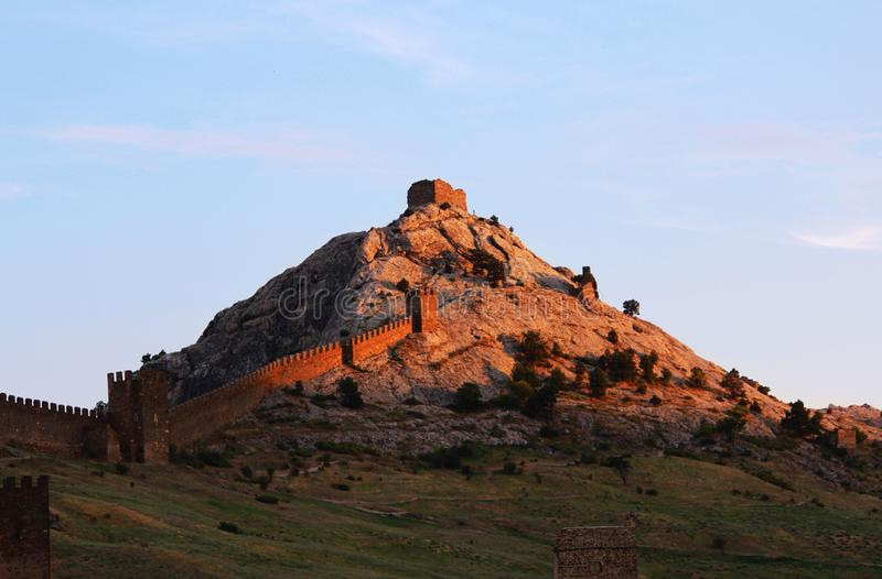 Berge teilweise bedeckt mit Waldsommer, die Republik von Krim Eine Ansicht der Genoese Festung, die durch das settin beleuchtet w lizenzfreie stockfotografie