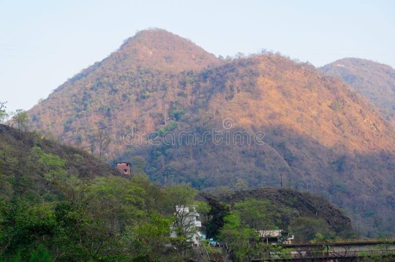 Berge und Bäume mit Gebäuden am haridwar shivpuri lizenzfreie stockfotos