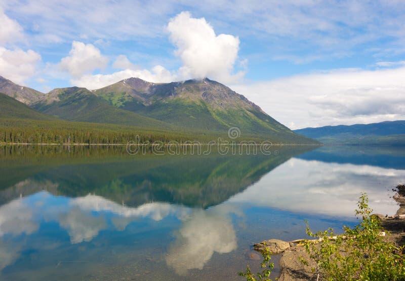 Berge und Wolken reflektiert im Wasser stockbilder