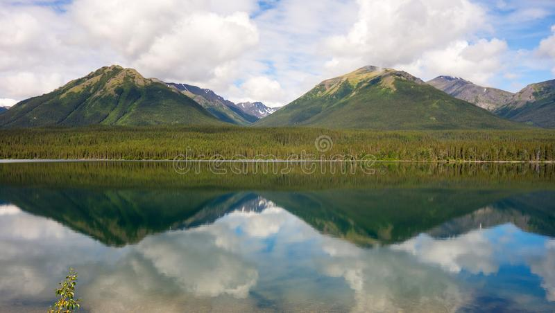 Berge und Wolken reflektiert im Wasser lizenzfreies stockbild