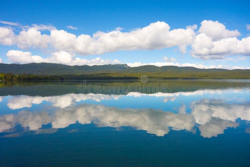 Berge und Wolken reflektiert im Wasser lizenzfreie stockfotografie