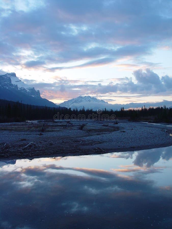 Berge und Wolken reflektierten sich im Fluss am Sonnenuntergang lizenzfreie stockfotos