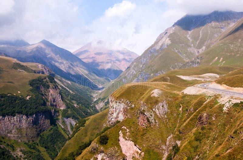 Bergen en bergweg in de herfst in Georgië Magische betoverende die aard, hooggebergte met witte sneeuw onder een blauwe hemel wor stock fotografie
