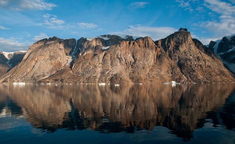 Bergen en ijsbergen die in kalm water, o-Fjord, Groenland worden weerspiegeld royalty-vrije stock foto