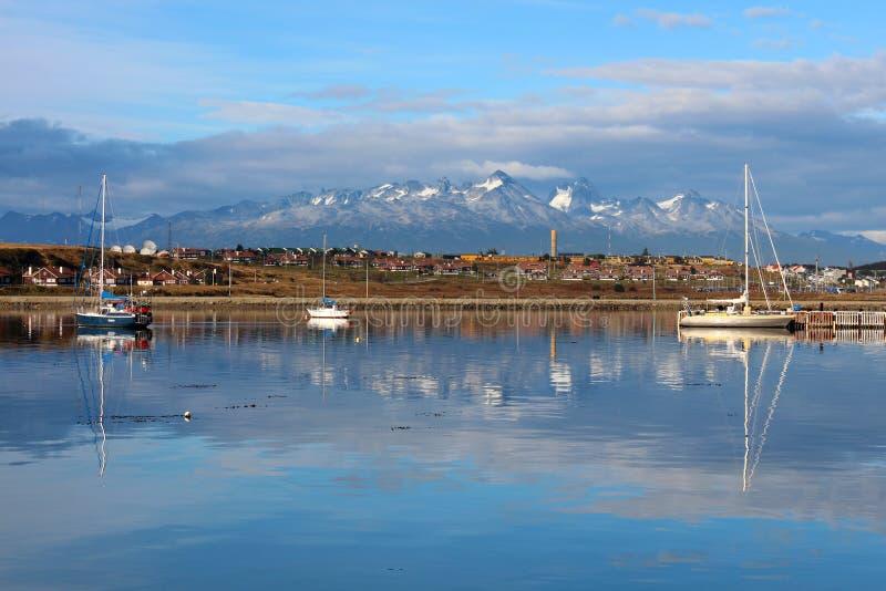 Bergen en stad Ushuaia die in water, Patagonië nadenken stock fotografie