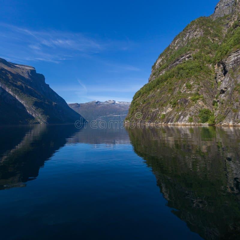 Bergen in Geiranger-fjord, blauwe overzees, hemel worden weerspiegeld die stock fotografie