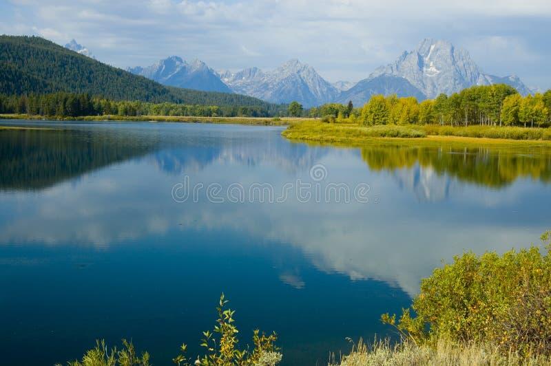 Bergen, hemel en dalingskleuren die in meer worden weerspiegeld royalty-vrije stock foto's