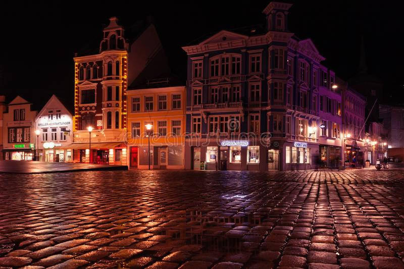 Bergen old town at night, empty town square. Bergen, Norway - November 17, 2017:  Bergen old town at night, empty wet town square with colorful illumination stock photography