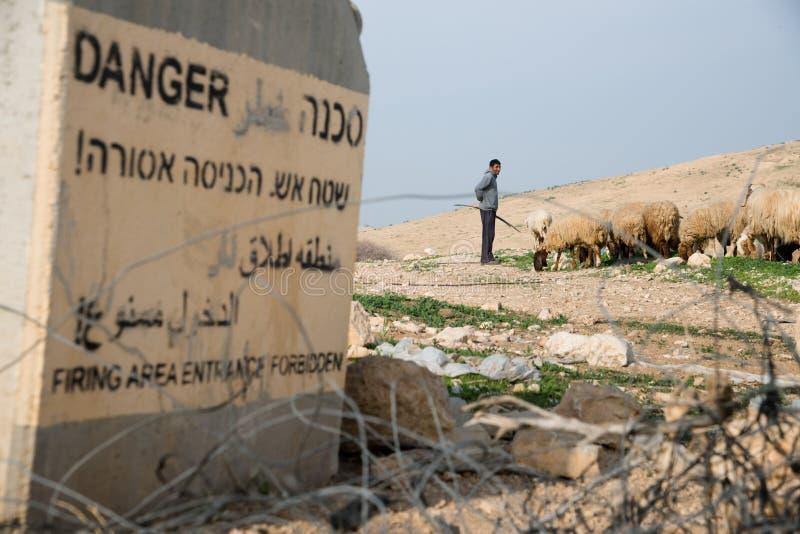Berger palestinien près de panneau d'avertissement militaire israélien photos libres de droits