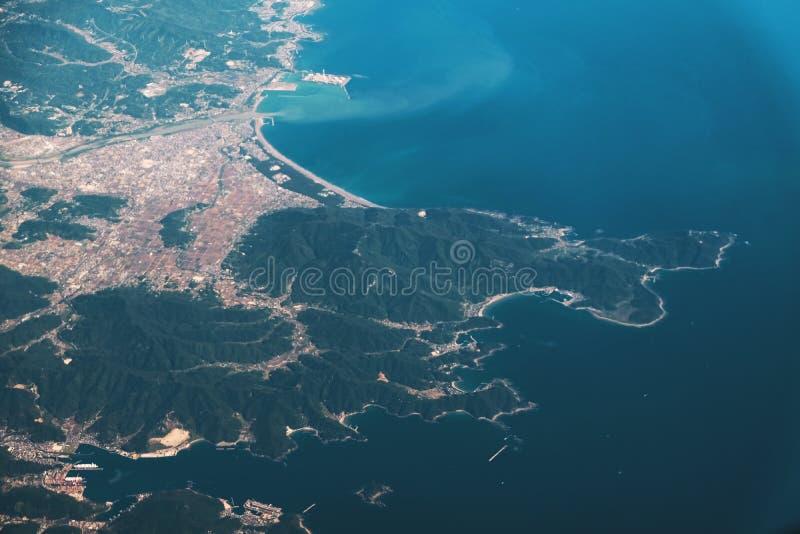 Berget och havet, sikt från flygplanfönster arkivbild