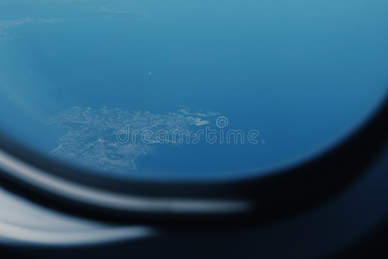 Berget och havet, sikt från flygplanfönster royaltyfri bild