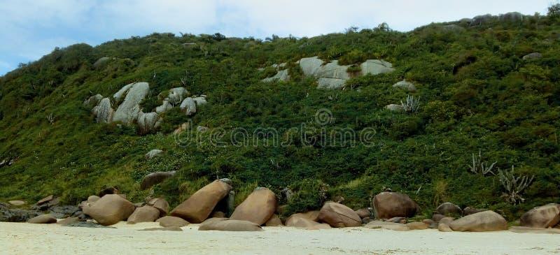 Berget och vaggar vid sandstranden royaltyfri bild