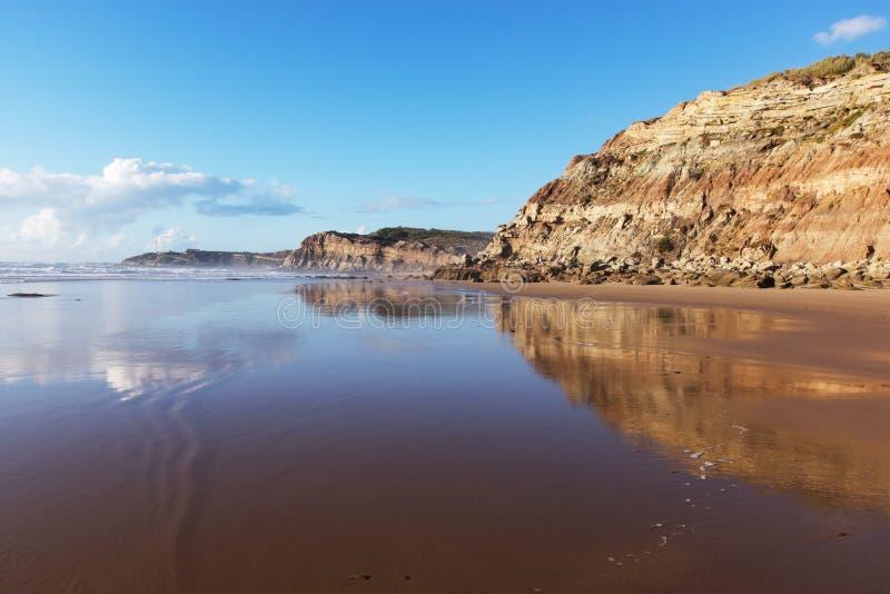 Berget reflekterade i det släta vattnet av stranden Areia Branca Lourinha Portugal, royaltyfri bild