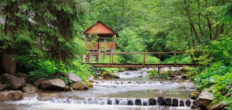 Bergflod, frodig vegetation och rekreationsområde med en bro och en gazebo Carpathian lägeställe, Ukraina, Europa wide arkivbilder