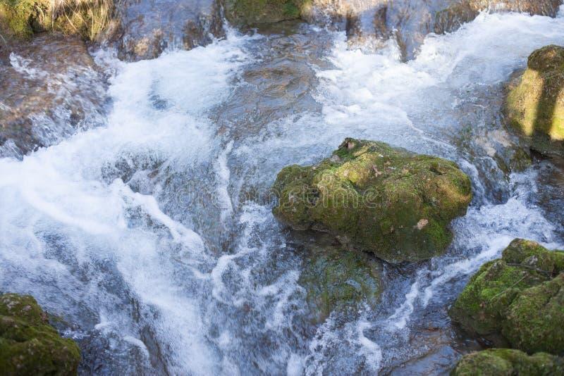 Bergflodkörning till och med stenen med mossa arkivbild