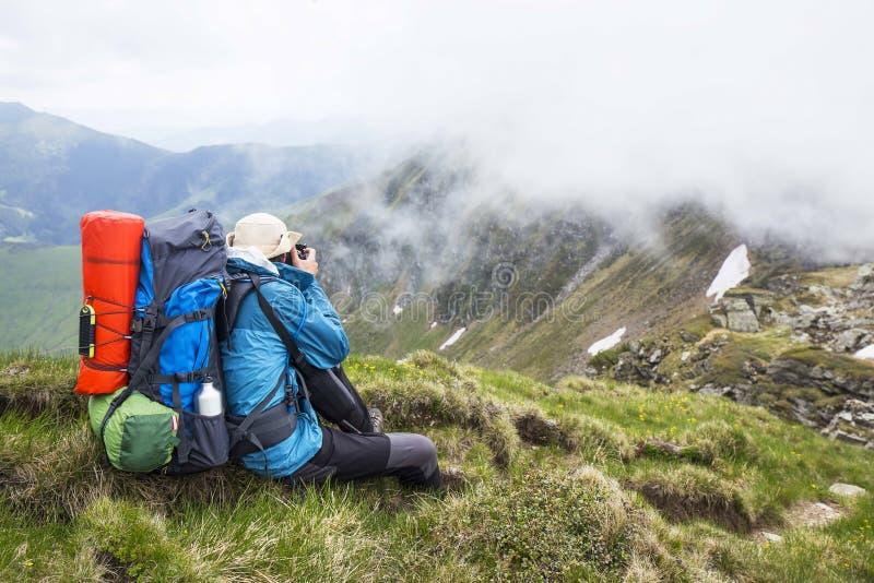 Bergfotograf och fotvandrare med ryggsäck- och utrustningoutd royaltyfri foto