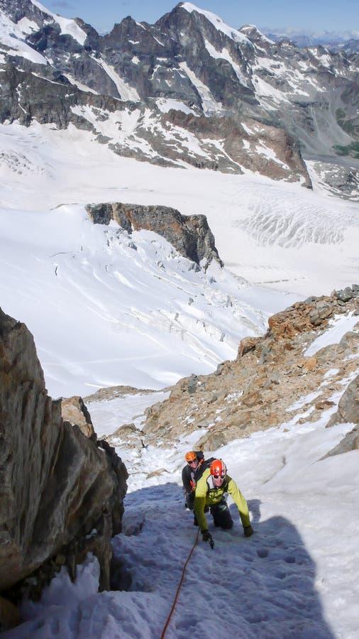 Berggids die mannelijke cliënt leiden tot de top van een hoge alpiene piek op een mooie de zomerdag stock afbeeldingen