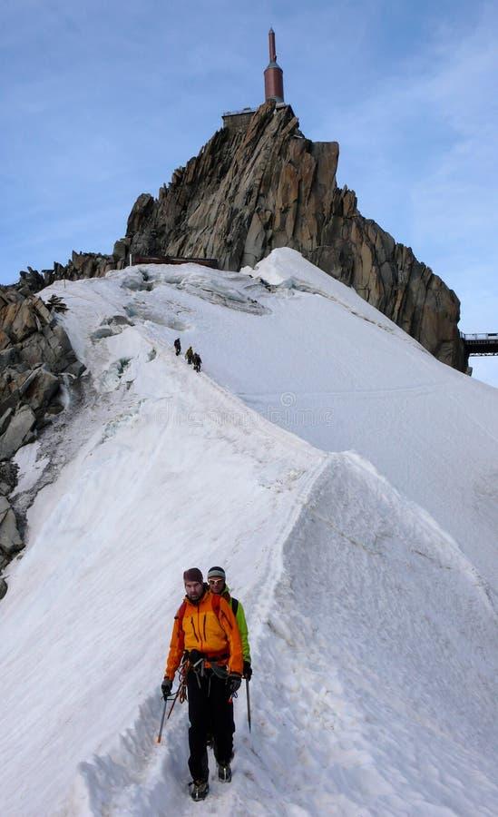 Berghandbok och en manlig klient på en snökant som heading ner från en hög toppmöte i de franska fjällängarna nära Chamonix arkivfoton
