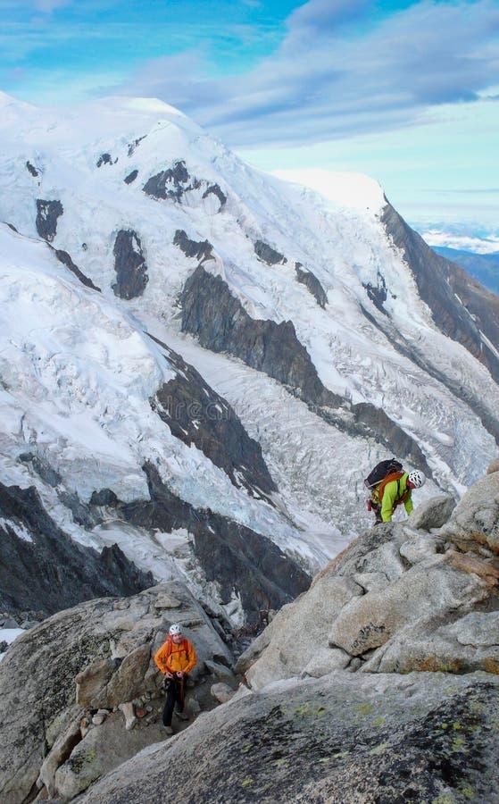 Berghandbok och en manlig klient på en stenig kantöverskrift in mot en hög toppmöte i de franska fjällängarna nära Chamonix arkivbilder