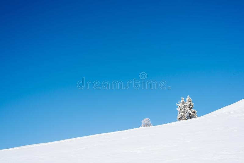 Berghelling met sneeuw en blauwe hemel wordt behandeld die royalty-vrije stock afbeeldingen