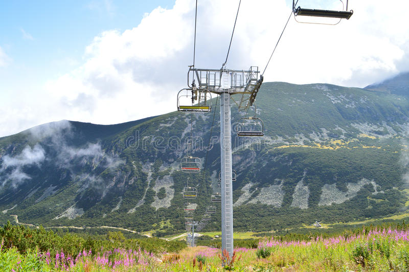 Berghelling met stoeltjeslift stock afbeeldingen