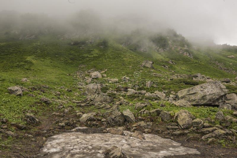 Berghelling met wolken wordt behandeld die stock fotografie