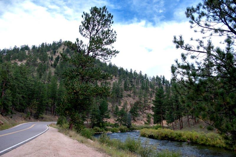 Berghuvudväg som buktar med en flod royaltyfria bilder