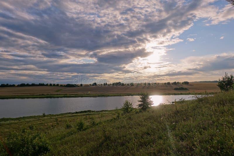 Bergigt landskap med lösa örter och whater på solnedgången royaltyfria bilder