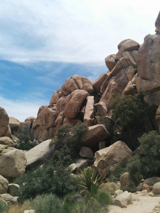 Bergkant met losse rotsen, groen, en hemel royalty-vrije stock afbeeldingen