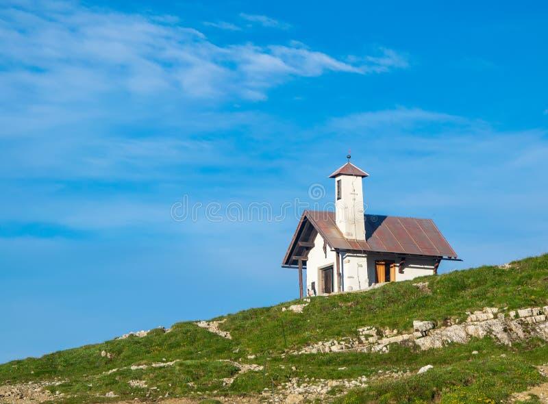 Bergkapell mot blå himmel Dolomites Italien royaltyfri bild