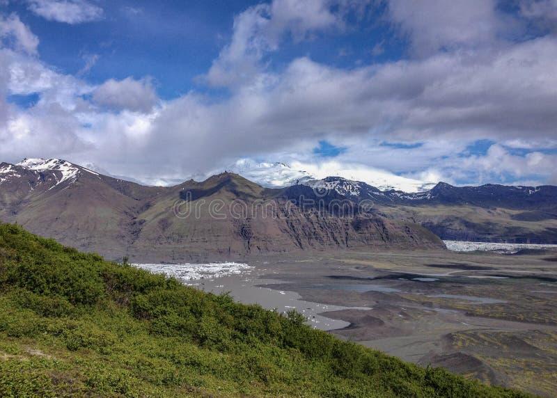 Bergketen Hafrafell met sneeuw, gletsjertong Skaftafellsjokull en groen bos met blauwe hemel in de zomer, Vatnajokull wordt behan stock afbeelding
