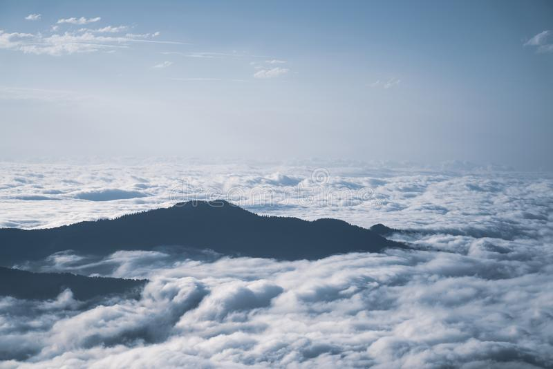 Bergkonturn ovanför molnen på soluppgång, beskådar uppifrån sikt av berg fotografering för bildbyråer