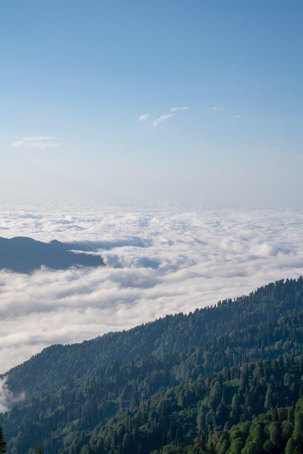 Bergkonturn ovanför molnen på soluppgång, beskådar uppifrån sikt av berg royaltyfria bilder