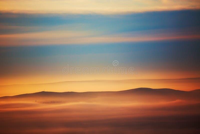 Berglaag in de straal van de ochtendzon en de wintermist royalty-vrije stock afbeeldingen