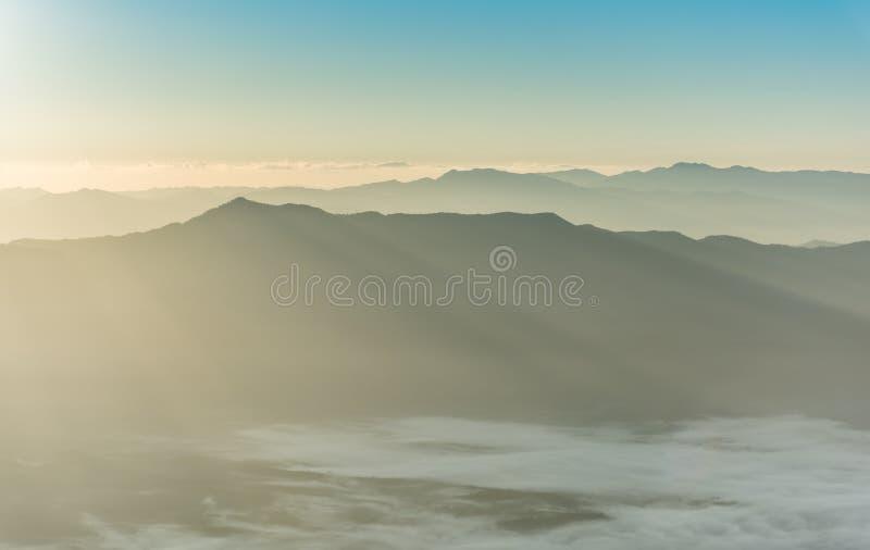 Berglaag in de straal van de ochtendzonsopgang en de wintermist royalty-vrije stock foto's