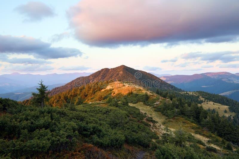 Berglandschaft mit schönem Sonnenuntergang, bewölktem Himmel und orangefarbenem Horizont Fantastische Landschaft im Herbst stockfotografie