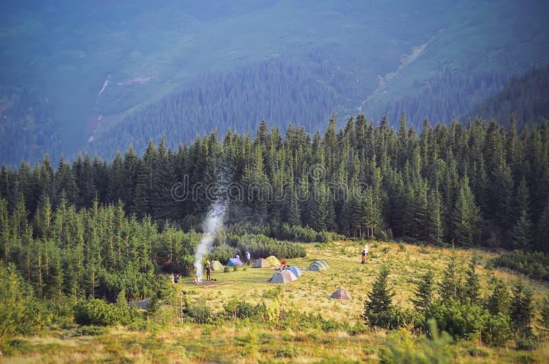 Berglandschaft am Sonnenschein Touristische Zelte im Wald lizenzfreie stockfotos