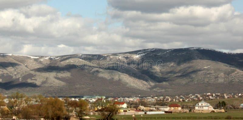 Berglandschap en dorp in de vallei, de uitlopers, de Krim Simferopol, toevluchtgebieden, hemel en wolken, gebieden en gras, in s stock foto's